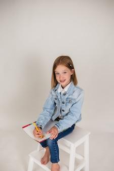 데님을 입은 어린 금발 소녀가 앉아 있고 흰색 배경에 있는 앨범에 공간 사본이 있는 그림을 그리고 있습니다. 어린이의 미술 교육
