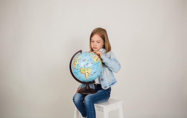 Маленькая блондинка в джинсовой ткани сидит на стуле с глобусом на белом фоне с копией пространства