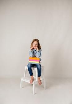Маленькая блондинка в джинсовой ткани сидит на стуле с учебниками на белом фоне с копией пространства