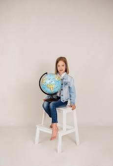 Маленькая блондинка в джинсовой ткани сидит с глобусом на белом фоне с местом для текста. обратно в школу