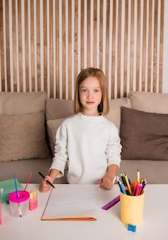 Маленькая блондинка сидит за столом и рисует на бумаге. искусство для детей