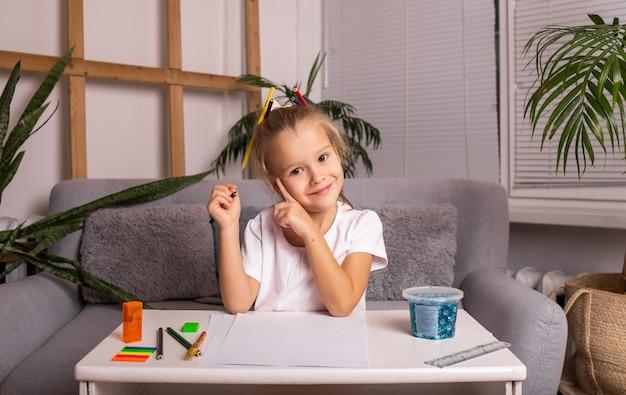 Маленькая блондинка сидит за столом и рисует карандашами на бумаге