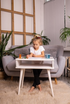 小さなブロンドの女の子がテーブルに座って、紙に鉛筆で描いています