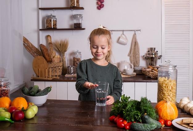 小さなブロンドの女の子が台所のテーブルに座って、ビタミンを飲んでいます