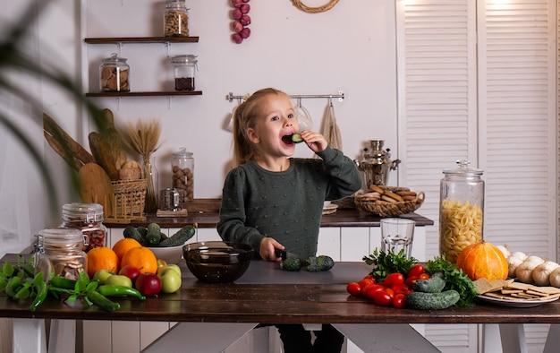 小さなブロンドの女の子が野菜や果物と一緒に台所のテーブルに座って、きゅうりを食べています