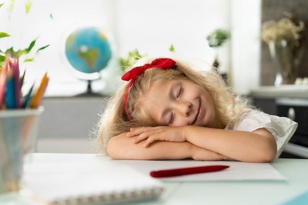 Маленькая блондинка учится, устала изучать ребенка, лежащего на столе школьница