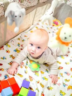 어린 금발 소녀는 장난감 사이에 있는 침대에 엎드려 큰 회색 눈으로 앞을 내다본다