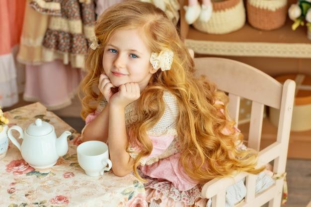 긴 머리를 가진 작은 금발은 테이블에 앉아 차를 마시고 차를 마시는 6 세의 아름다운 소녀를 미소 짓습니다. 아기 세련된 스타일