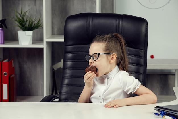 안경을 쓴 작은 보스 소녀가 사무실 책상에 앉아 컵케이크를 먹고 있다