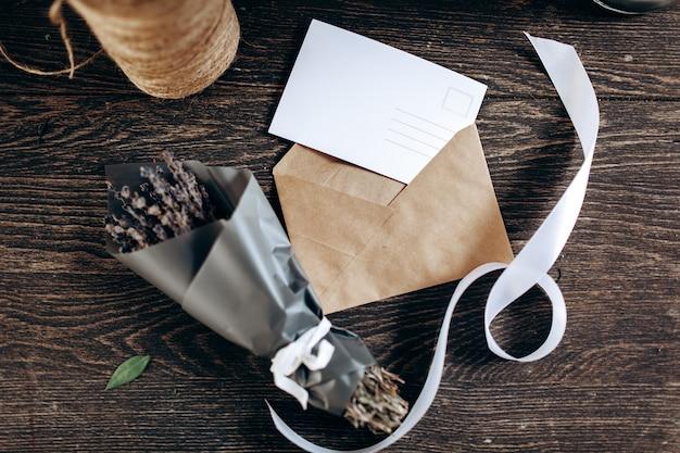 На столе лежит небольшой букет цветов, упакованный в бумажный конверт для открытки и белая лента.