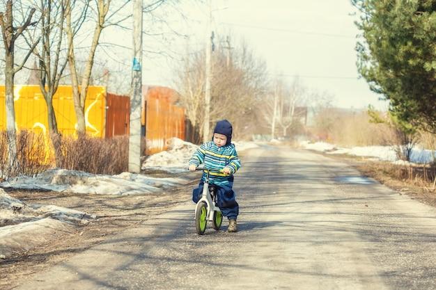 2 세 소년이 마을의 도로에서 균형 자전거를 타는 법을 배웁니다.