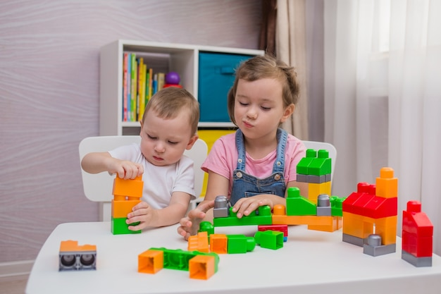 어린 소년과 소녀가 방의 테이블에서 생성자 게임을하고 있습니다.