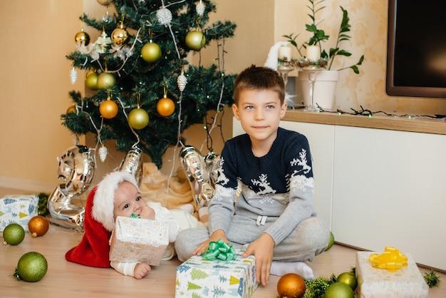 Маленький мальчик и его брат играют с подарками под праздничной елкой