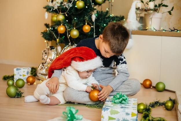 小さな男の子と彼の兄弟は、お祝いのクリスマスツリーの下で贈り物で遊ぶ