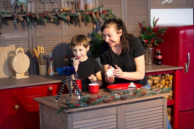 小さな男の子とお母さんが、家庭の台所のスマートフォンでyoutubeにストリームやビデオを録画しています。