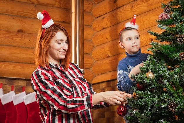 小さな男の子と母親がカントリーハウスで人工的なクリスマスツリーをガラス玉で飾ります