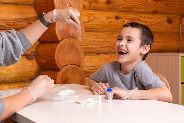 어린 소년과 어머니가 화학 원소가 담긴 가방을 열고 화학 원소를 준비합니다. 화학 교육 및 훈련 개념.