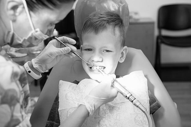 Маленький мальчик на приеме у стоматолога в стоматологической клинике. детская стоматология, детская стоматология. черная и белая фотография в стиле ретро. здоровье и гигиена полости рта