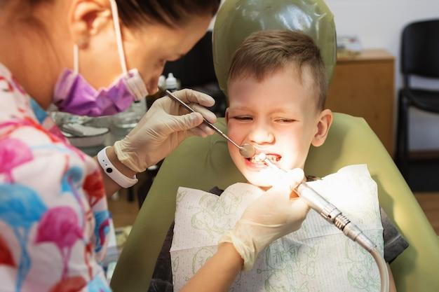 Маленький мальчик на приеме у стоматолога в стоматологической клинике.