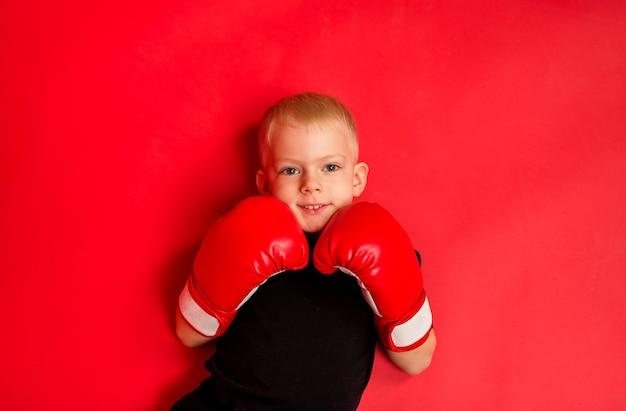 小さな男の子のボクサーは赤いボクシンググローブに横たわっています