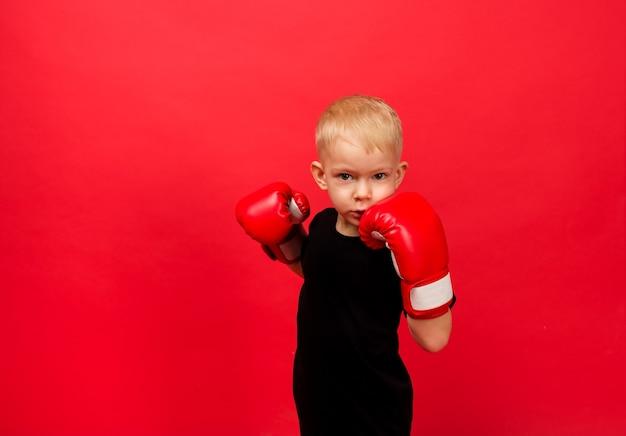 小さな男の子のボクサーは、赤のボクシンググローブでパンチを作ります
