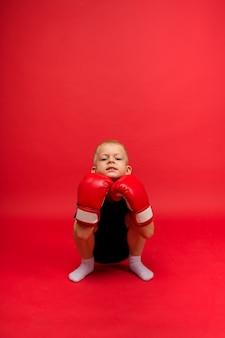 小さな男の子のボクサーは赤の赤いボクシンググローブでしゃがむ
