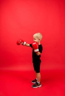 어린 소년 권투 선수가 옆으로 서서 빨간색 권투 장갑을 끼고 펀치를합니다.