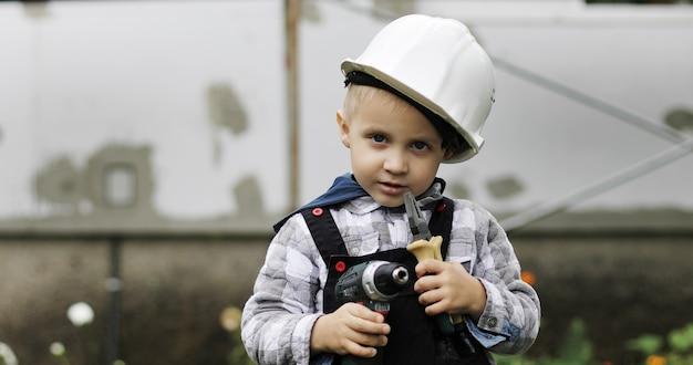 白いヘルメットの小さな男の子ビルダーは、ペンチとドリルまたはドライバーで足場に座っています