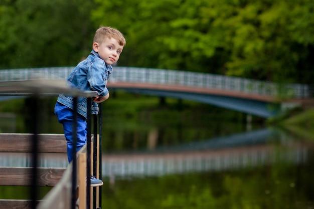어린 소년이 공원에서 다리 난간을 올라갑니다. 익사의 위협. 어린이에게 위험합니다.