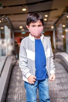 Маленький мальчик в защитной маске поднимается по эскалатору универмага
