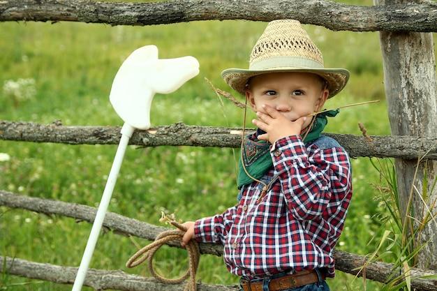 自然の柵の近くにロープで帽子をかぶった小さな男の子のカウボーイ