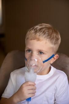 小さな男の子が自宅でネブライザーを使って吸入します彼は病気です自宅で咳喘息を助けます