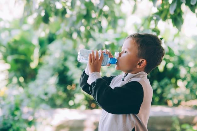 어린 소년은 야외에서 파란색 병으로 물을 마신다