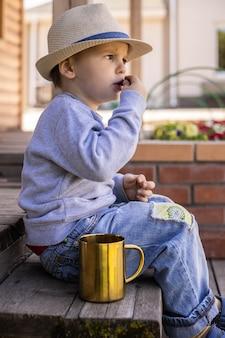 어린 소년은 황금 머그에서 파란 인동덩이를 먹습니다.