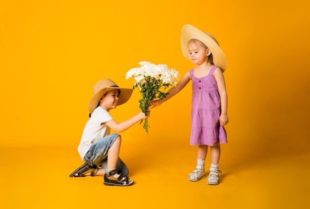어린 소년은 텍스트를위한 공간이있는 노란색 표면에 밀짚 모자를 쓴 어린 소녀에게 꽃 꽃다발을 제공합니다.