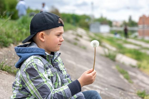 Маленький мальчик держит в руке одуванчик и смотрит на него