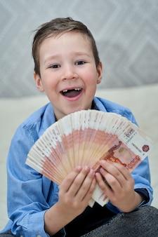 어린 소년은 그의 손 초상화에 5 천 달러 지폐를 보유