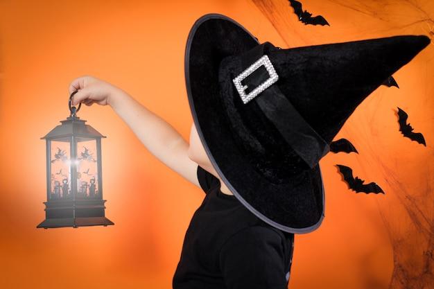 검은 모자를 쓴 어린 소년이 주황색 배경에 빛나는 등불을 들고 있습니다.