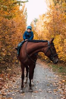 파란 재킷을 입은 어린 소년이 가을 공원에서 말을 타고 있다
