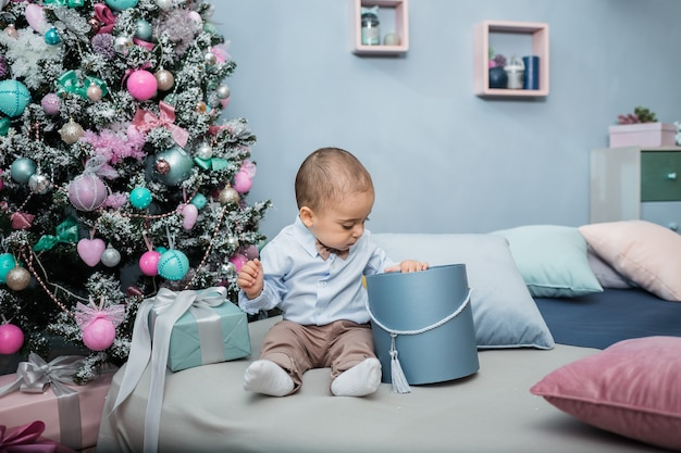 Маленький мальчик в синей рубашке сидит в комнате на кровати и открывает подарок на фоне елки.