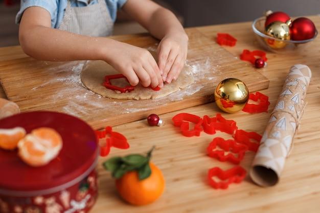 Маленький мальчик в голубой рубашке делает печенье с помощью формочки для печенья.