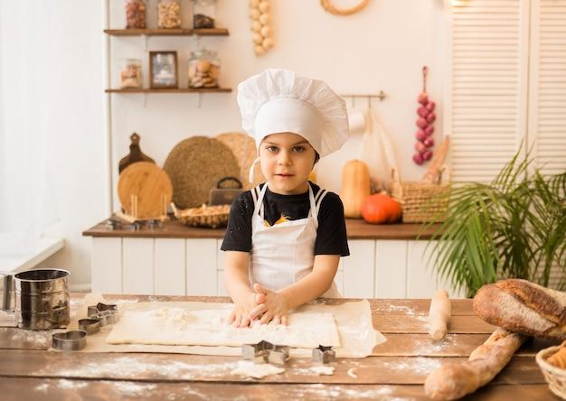 요리사의 모자와 앞치마에있는 어린 소년이 부엌의 나무 테이블에서 반죽을 준비합니다.