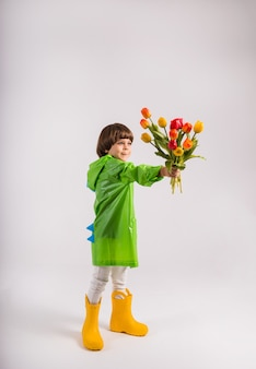 Маленький мальчик в зеленом плаще и желтых резиновых сапогах дарит букет разноцветных тюльпанов на белом фоне с местом для текста