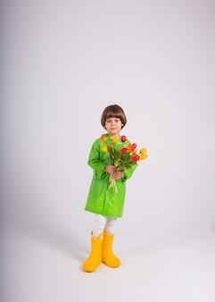 Маленький мальчик в зеленом плаще и желтых резиновых сапогах держит букет разноцветных тюльпанов на белом фоне с копией космоса