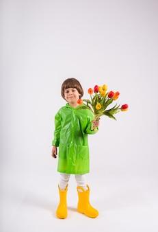 Маленький мальчик в зеленом плаще и желтых резиновых сапогах держит букет разноцветных тюльпанов на белом фоне с местом для текста