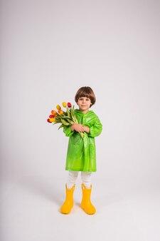 Маленький мальчик в зеленом плаще и желтых резиновых сапогах стоит с букетом разноцветных тюльпанов на синем фоне с местом для текста