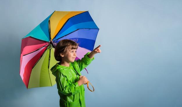 녹색 비옷을 입은 어린 소년은 다양한 색상의 우산을 들고 파란색 배경에 텍스트를 위한 장소가 있는 측면을 가리킵니다