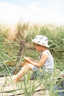 帽子をかぶった男の子が葦で釣りをしています。