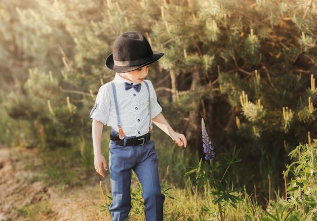 晴れた日の夏、帽子をかぶった男の子が自然の中を歩きます。国の自然