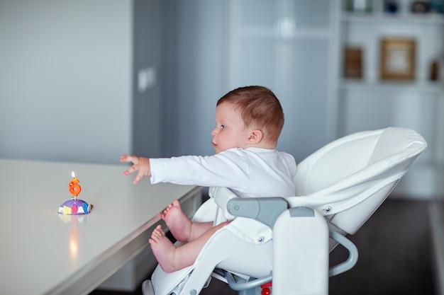 유아용 높은 의자에 앉은 어린 소년이 6이라는 숫자가 적힌 초를 들고 케이크에 손을 뻗습니다. 고품질 사진